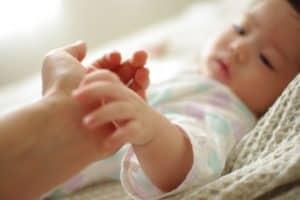 乳幼児がお母さんの手を握る